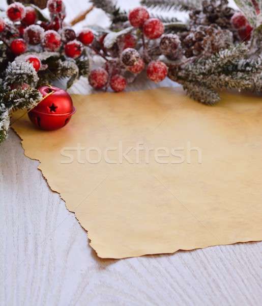 Snowed fur-tree branch with berries above wrapping paper Stock photo © asturianu