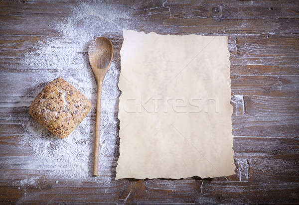 Bun with sesame, scattered flour, spoon and baking paper Stock photo © asturianu