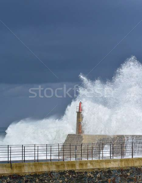 Stormy wave over old lighthouse and pier of Viavelez. Stock photo © asturianu