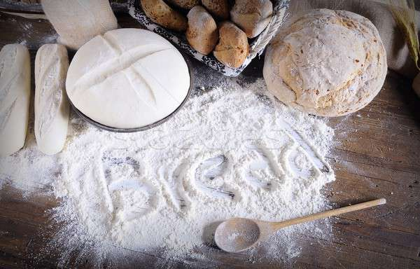 Stock photo: Word 'bread' written on flour scattered on wooden table
