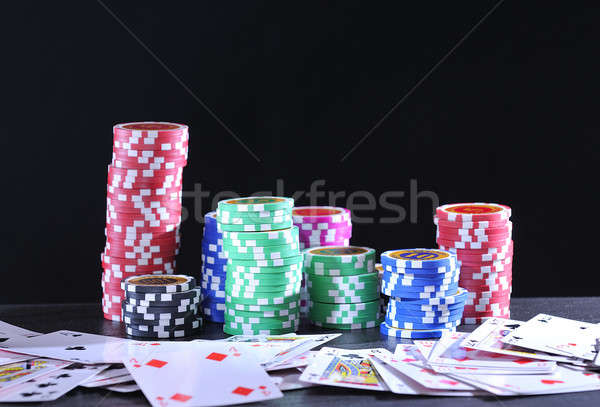 Rolls of poker chips and cards on black background Stock photo © asturianu