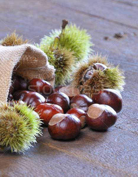 Close-up of chestnuts scattered on wooden table Stock photo © asturianu