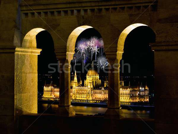 Stock photo: Hungarian Parliament through Fishermans bastion with fireworks