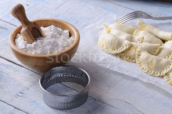 Raw dumplings, bowl with flour and cutter on wooden table Stock photo © asturianu