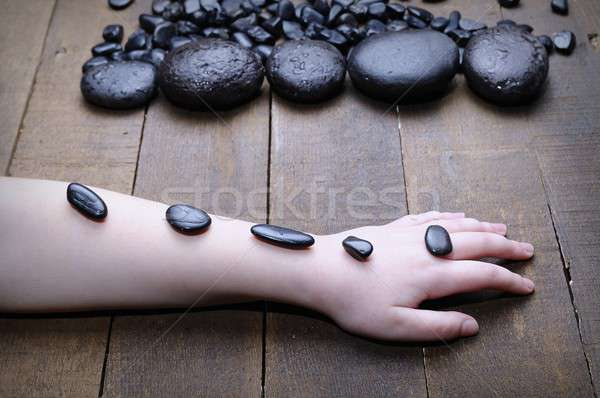 Someone's hand covered with spa stones Stock photo © asturianu