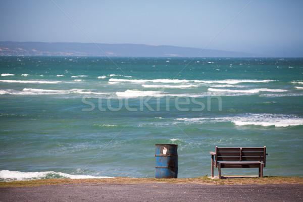 Wooden bench and iron barrel dustbin overlooking ocean Stock photo © avdveen