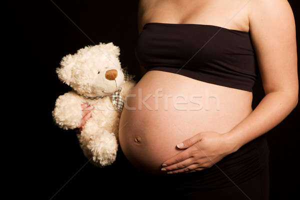 Young expectant Caucasian woman holding teddy bear Stock photo © avdveen