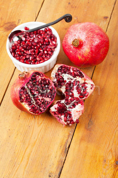 Pomegranate pips in a bowl with whole fruit on wooden surface Stock photo © avdveen
