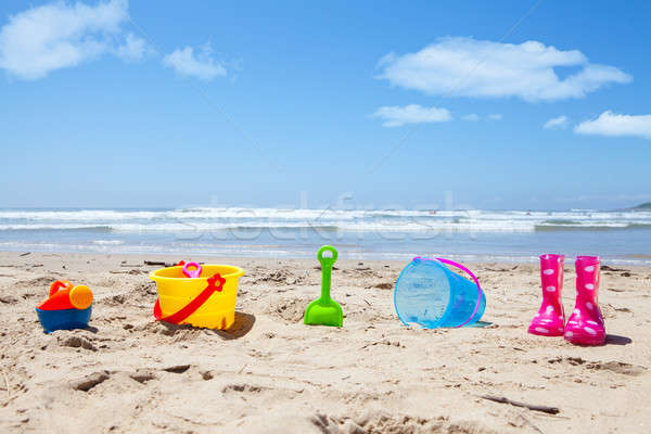 Colorful plastic toys and gumboots on beach sand Stock photo © avdveen