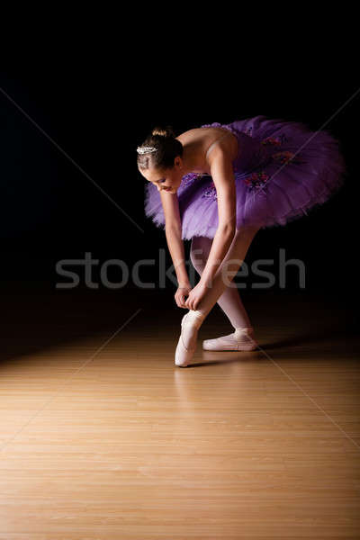 Stock photo: Young female ballerina adjusting her shoes