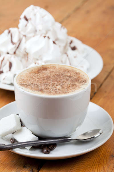 Cappuccino with foam and meringues on white plate Stock photo © avdveen