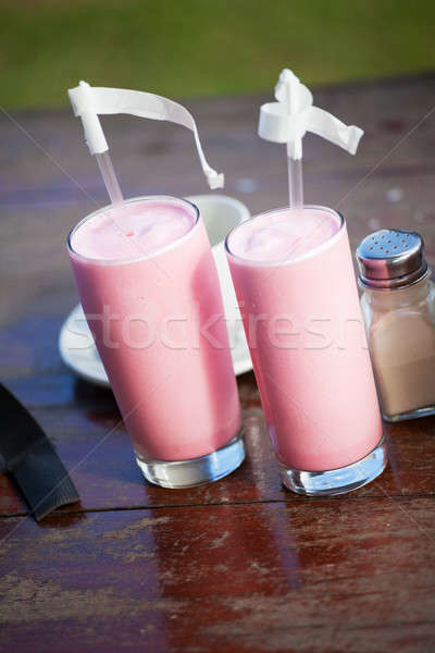 Two glasses with strawberry milkshake and straws Stock photo © avdveen