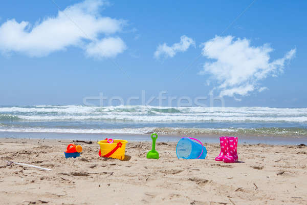Colorful plastic beach toys lying on the beach sand Stock photo © avdveen