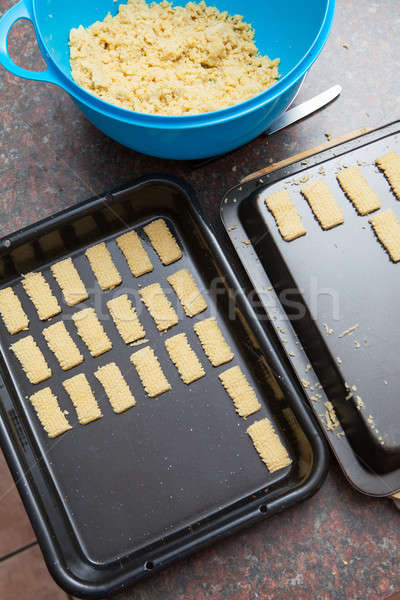 Raw cookie dough being cut and packed onto baking tray Stock photo © avdveen