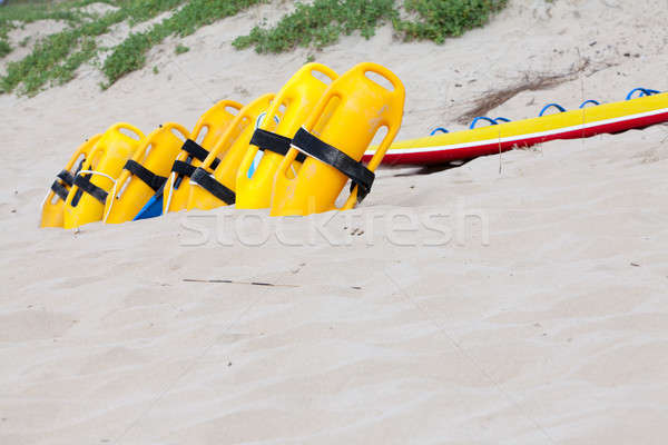 Row of bright yellow floatation devices on beach Stock photo © avdveen