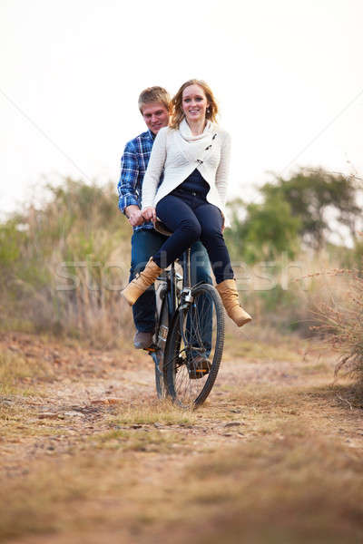 Happy couple riding old bicylce on dirt road Stock photo © avdveen