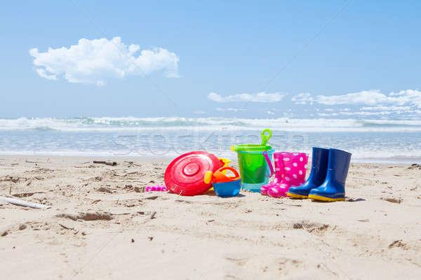 Műanyag játékok tengerparti homok színes felhők narancs Stock fotó © avdveen