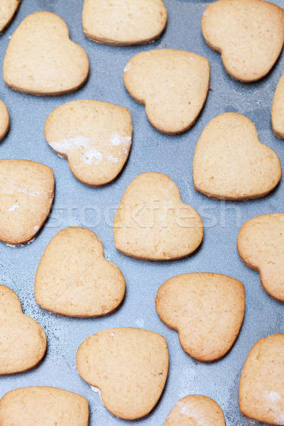 Rows of heart shaped biscuits on metal baking tray Stock photo © avdveen