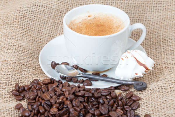 Delicious freshly brewed cup of coffee with whole beans on burla Stock photo © avdveen