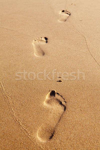 Stock photo: Three human footprints on the beach sand