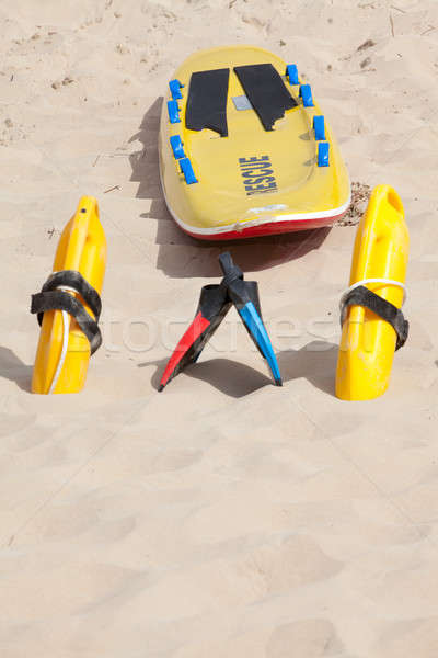 Lifesaving raft, floation devices and swimming fins on beach Stock photo © avdveen