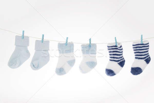Blue and white baby socks on clothesline, isolated Stock photo © AvHeertum