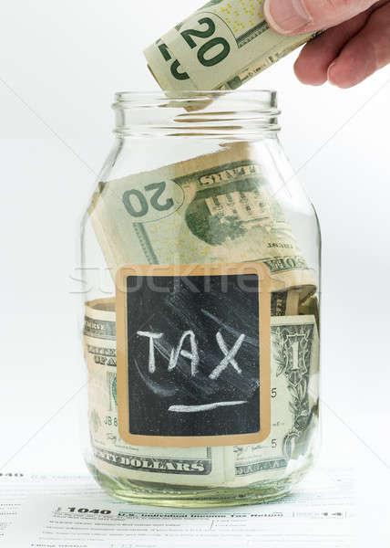 Hand inserting money into saving jar or bank Stock photo © backyardproductions