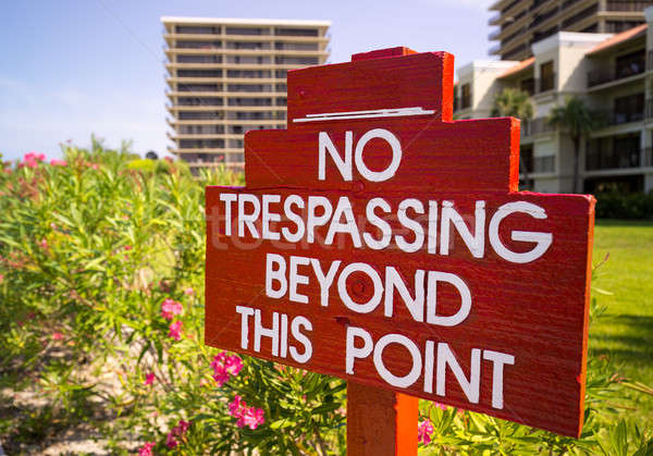 No Trespassing sign in red by flower gardens Stock photo © backyardproductions