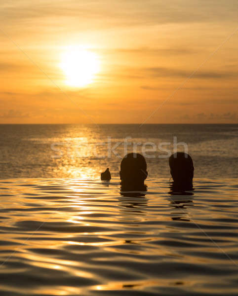 Infinity edge pool with sea underneath sunset Stock photo © backyardproductions