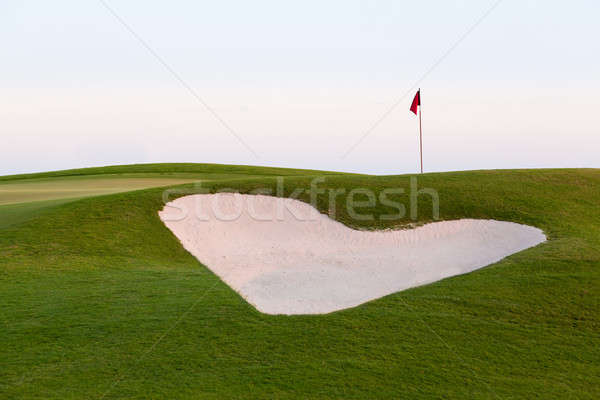 Heart shaped sand bunker in front of golf green Stock photo © backyardproductions