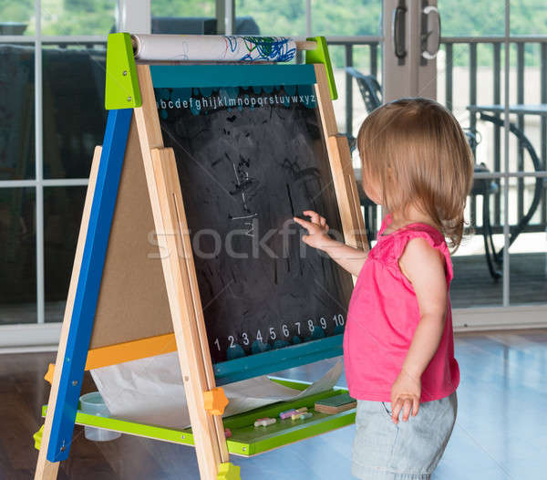 Young baby girl drawing at blackboard Stock photo © backyardproductions