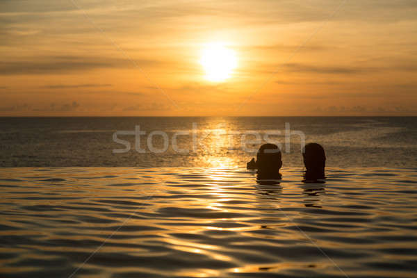 Silhouetted heads against infinity edge pool Stock photo © backyardproductions