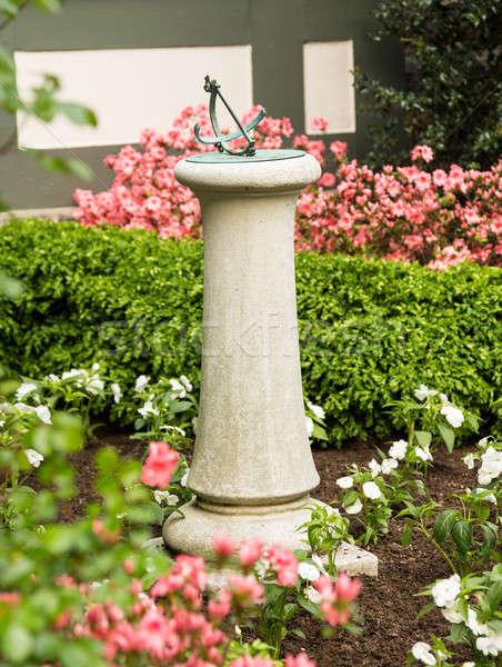 Concrètes pierre cadran solaire lit de fleurs bronze jardin Photo stock © backyardproductions