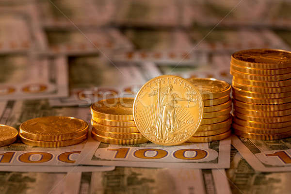 Stock photo: Gold coins stacked on new design 100 dollar bills