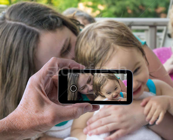 Mother and baby girl in smartphone snapshot Stock photo © backyardproductions