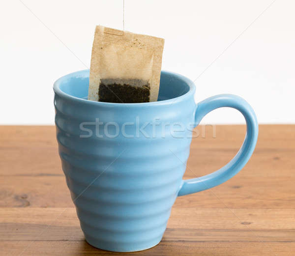 Brown organic green tea bag lowered in mug Stock photo © backyardproductions