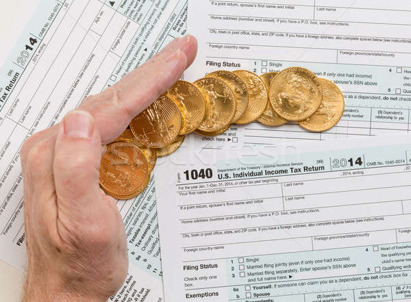 Solid gold coins on 2014 form 1040 Stock photo © backyardproductions