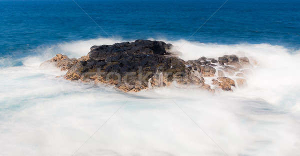 Long duration shot of waves flowing over lava rock Stock photo © backyardproductions