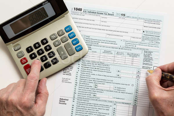 Pen and calculator on 2015 form 1040 Stock photo © backyardproductions