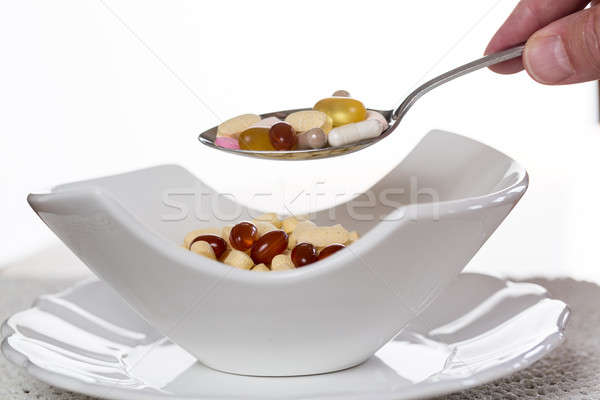 Spoon of vitamins over bowl of tablets Stock photo © backyardproductions