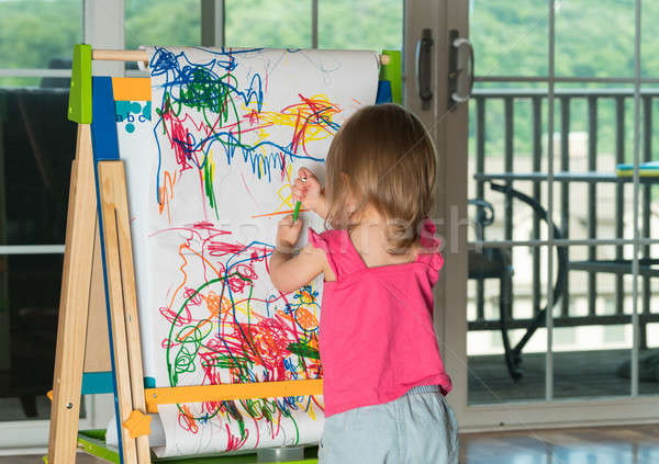 Young baby girl drawing at easel Stock photo © backyardproductions