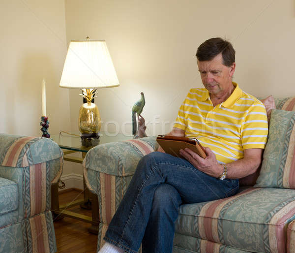 Boomer reading on tablet computer Stock photo © backyardproductions