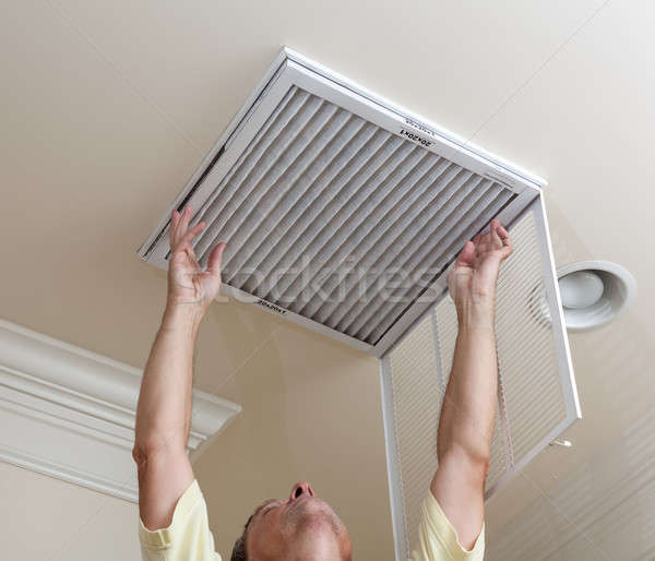 Senior man opening air conditioning filter in ceiling Stock photo © backyardproductions