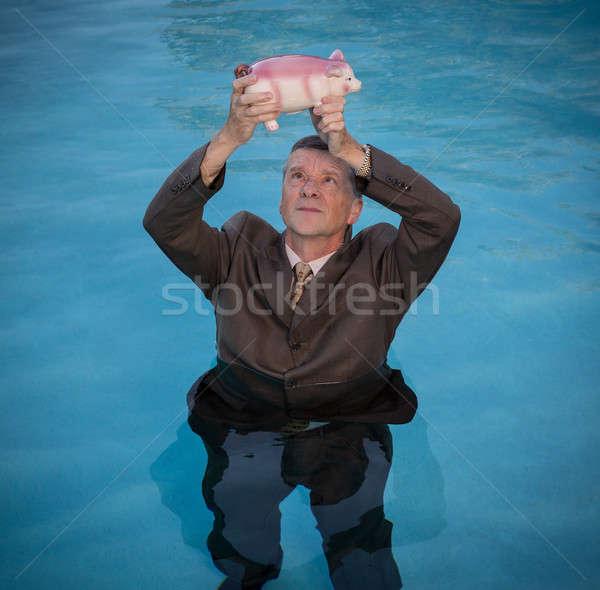 Senior man holding piggy bank above water Stock photo © backyardproductions