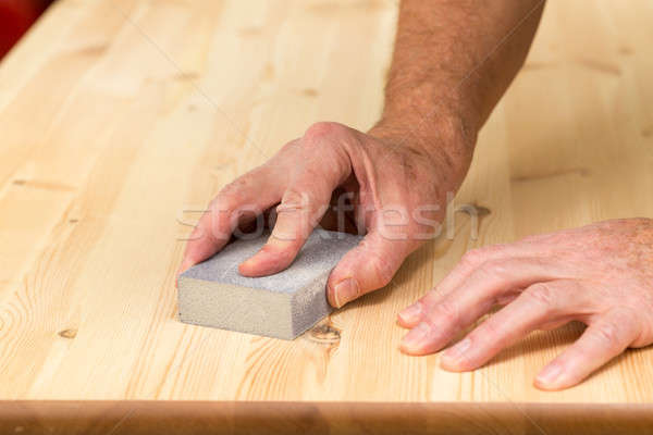 Mans hand on sanding block on pine wood Stock photo © backyardproductions