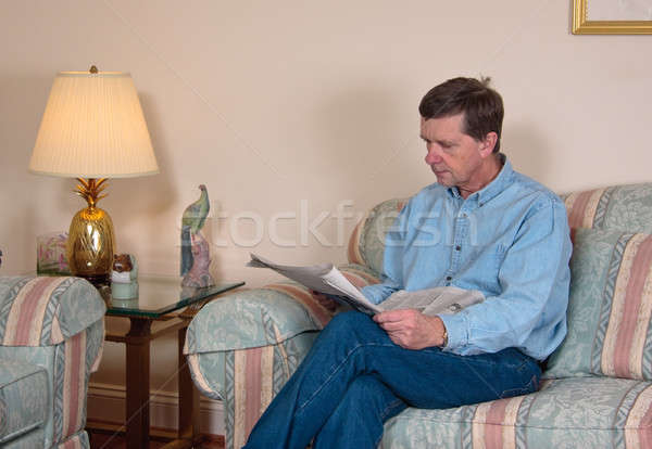 Middle-aged man relaxes on sofa in modern living room Stock photo © backyardproductions