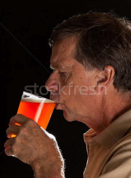 Senior man sipping from pint glass beer Stock photo © backyardproductions