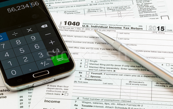 Pen and smartphone on 2015 form 1040 Stock photo © backyardproductions