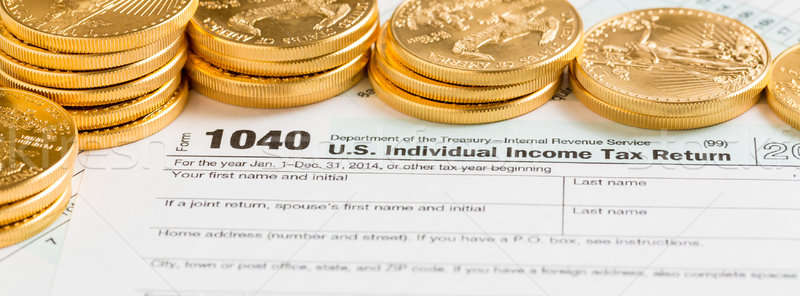 Stock photo: Solid gold coins on 2014 form 1040