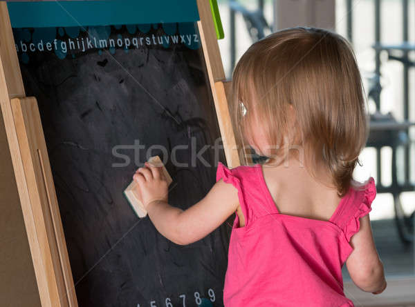 Young baby girl cleaning a blackboard Stock photo © backyardproductions